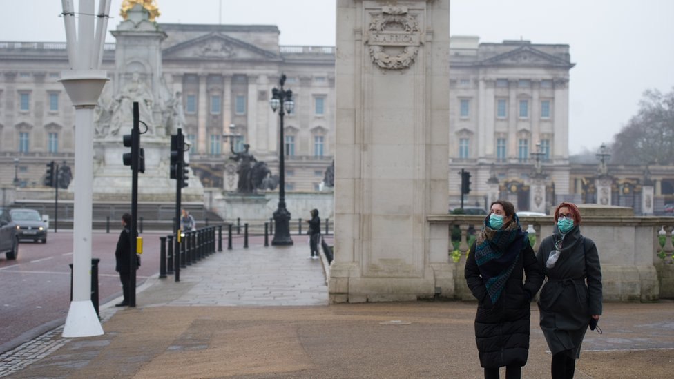 Two people outside Buckingham Palace wear a mask