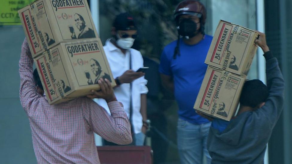 Muškarci nose kutije sa alkoholom