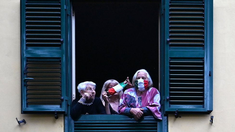 People with protective masks look from their windows at artists performing in the courtyard of a popular apartment building in Rome