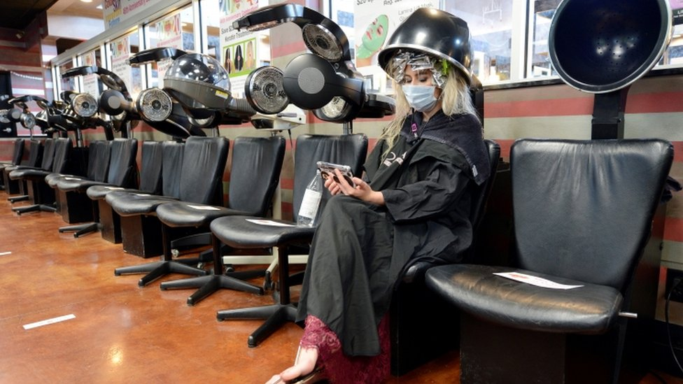 A customer wearing a face mask sits under a dryer at an empty salon in Marietta, Georgia