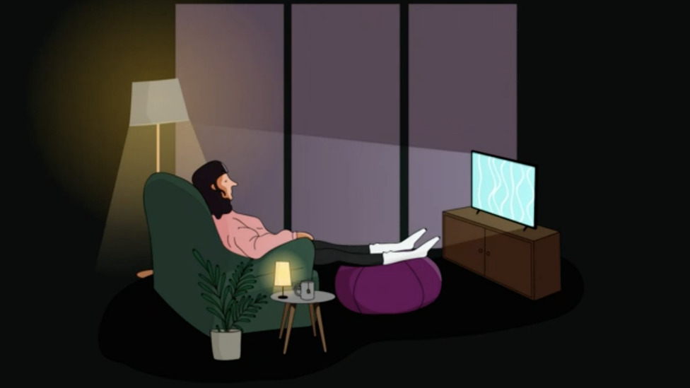 A woman watching TV closely at night