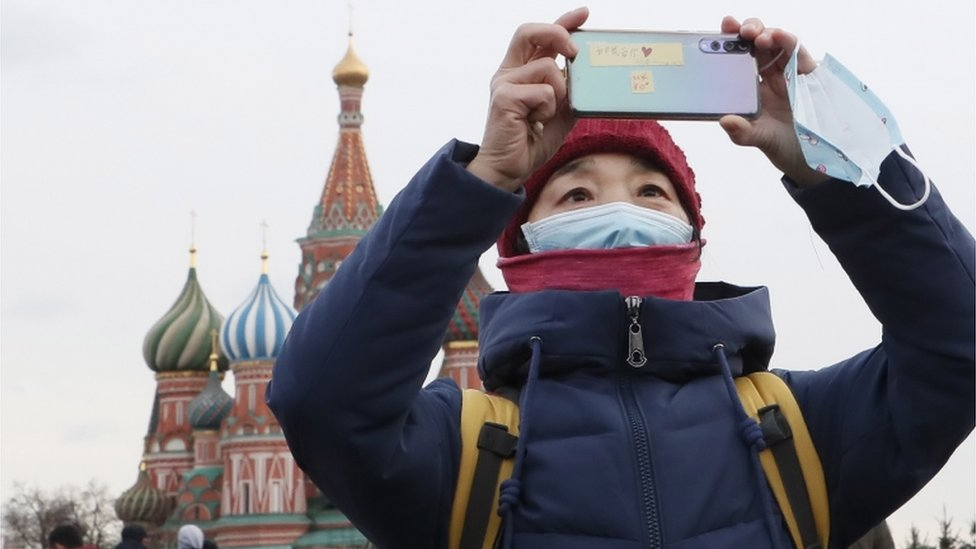 A Chinese tourist wearing a medical protection mask walks at the Red Square in Moscow, Russia, 26 January 2020