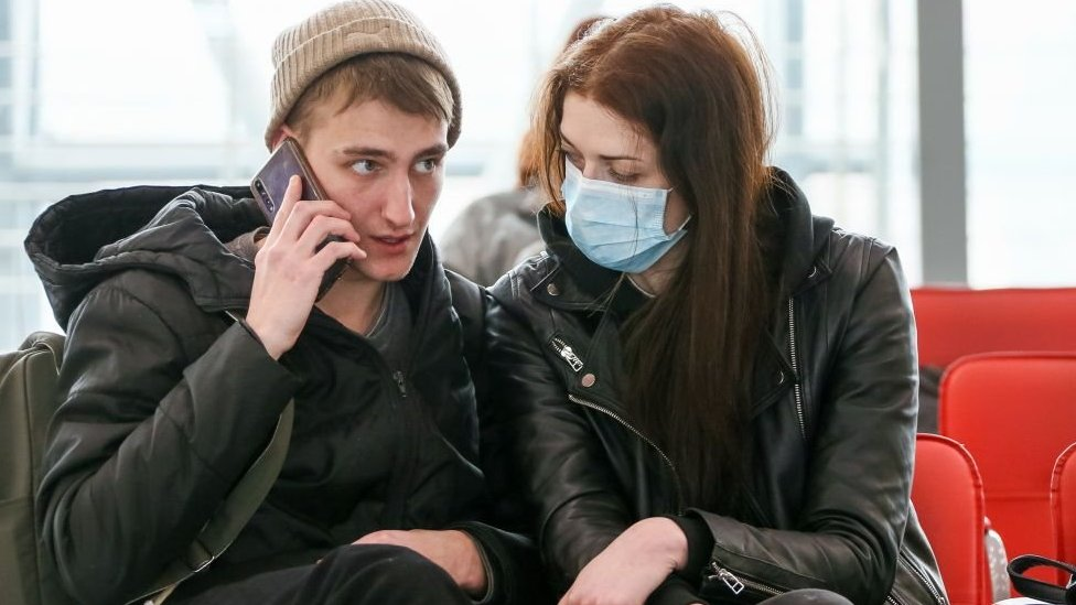 A young woman wearing a face mask looks at her unmasked partner at a train station in the Russian city of Sochi