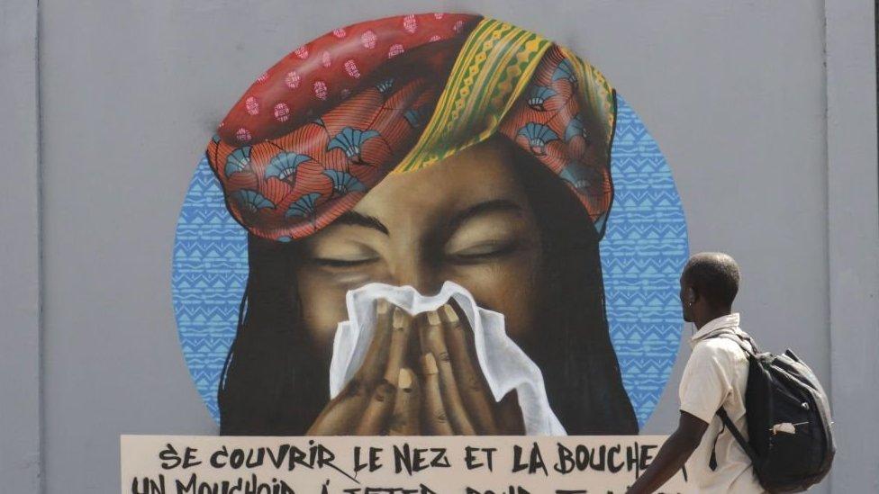 grafit u dakaru koji podseća ljude da treba da nose maske