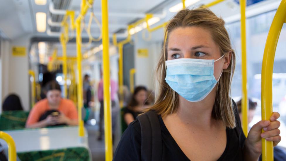 žena s maskom u autobusu