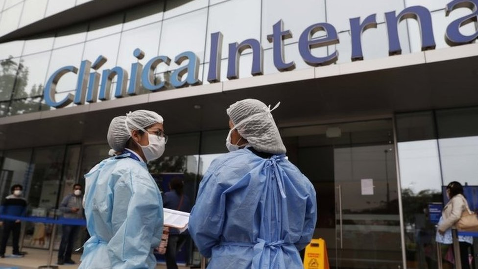 Health personnel stand outside of a private clinic after the last-minute agreement reached between the Government and private clinics to reduce health care prices during the pandemic, in Lima, Peru, 25 June 2020