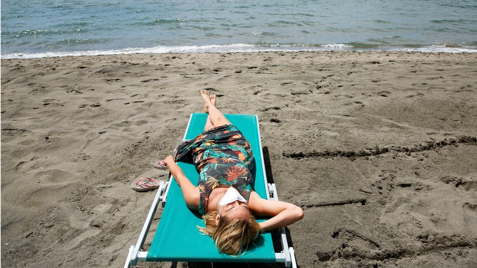 """A woman wearing a face mask sunbathes at the beach after it officially reopened for the first time following the country""""s strict coronavirus disease (COVID-19) lockdown, in Fregene, near Rome, Italy,"""