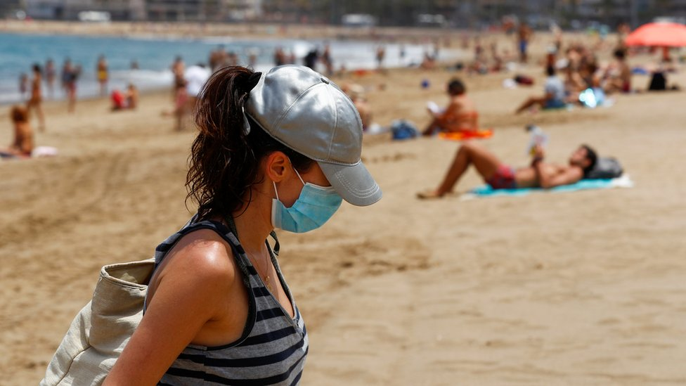 A woman with a face mask leaves the Las Canteras beach as some Spanish provinces are allowed to ease lockdown restrictions during phase two, amid the coronavirus disease (COVID-19) outbreak, on the island of Gran Canaria, Spain