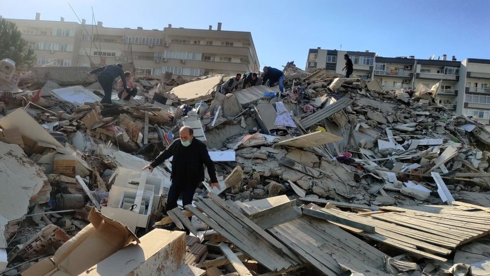 A man walks among debris of collapsed buildings after a magnitude 6.6 quake shook Turkey's Aegean Sea coast