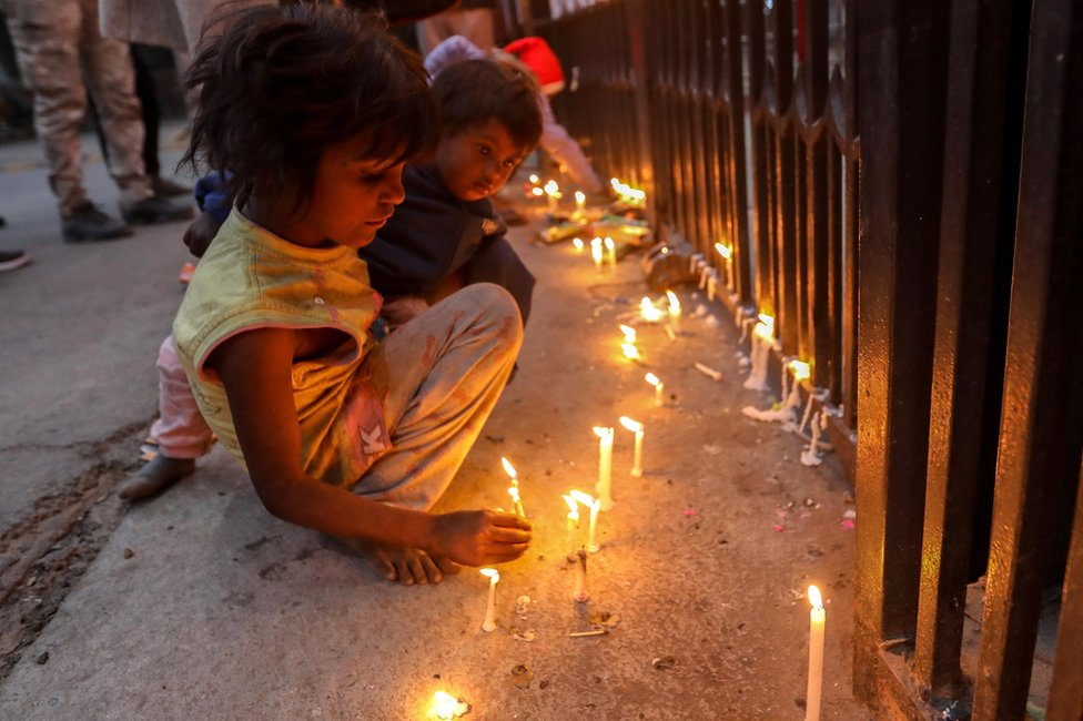 Children light candles at the entrance gate of the Sacred Heart Cathedral in Delhi, India. Photo: 24 December 2020