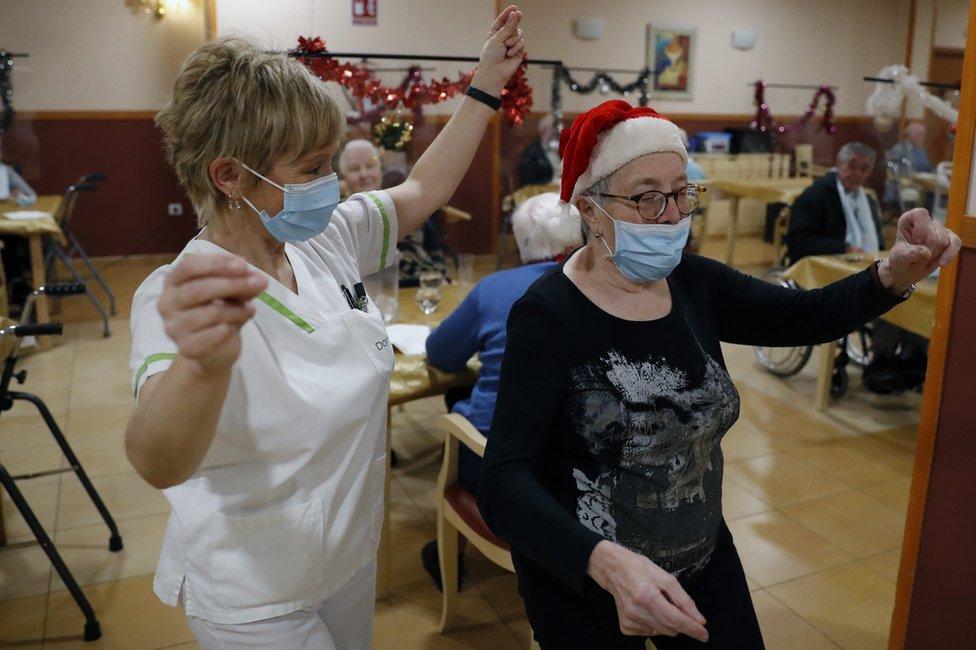 Elderly residents and a nurse celebrate Christmas in Santiago de Compostela, Spain. Photo: 24 December 2020