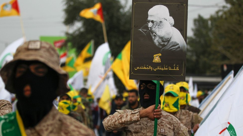 Kataib Hezbollah militia fighters hold up a poster showing Qasem Soleimani and Abu Mahdi al-Muhandis at their funeral in Baghdad (4 January 2019_