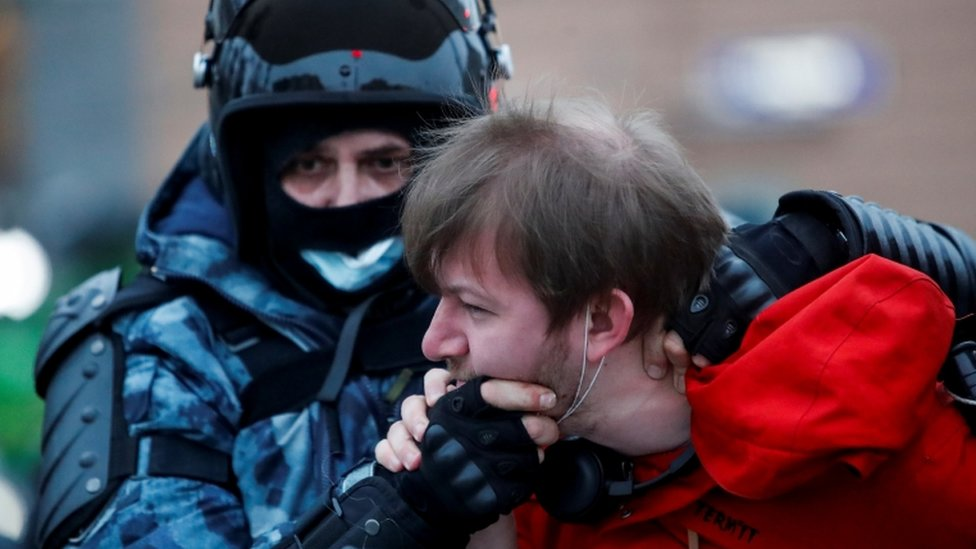 A law enforcement officer detains a man while holding him by the face in Moscow