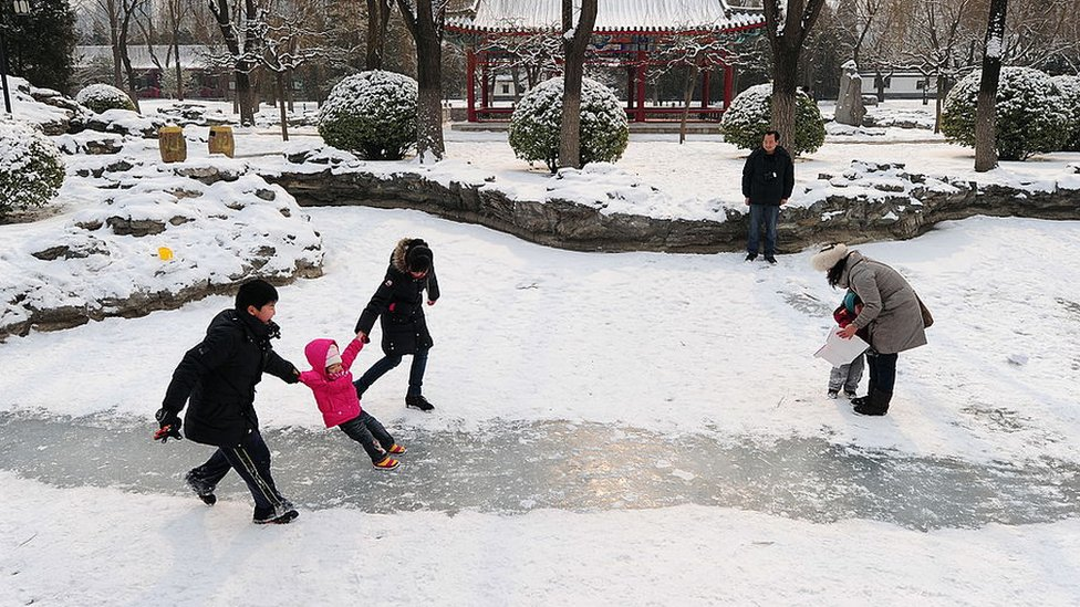 People play in the snow at a Beijing park in February 2011