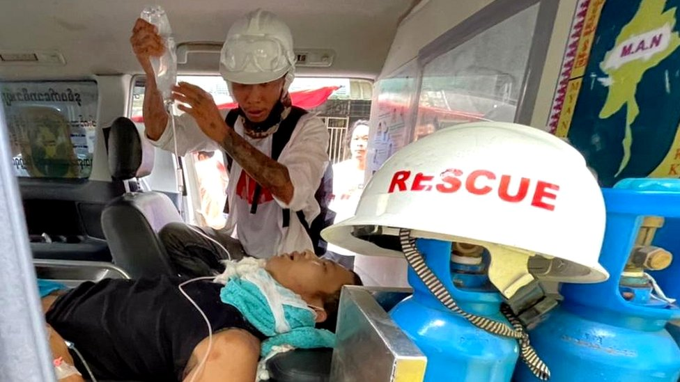 Emergency workers treat an injured man in Yangon's Hledan township
