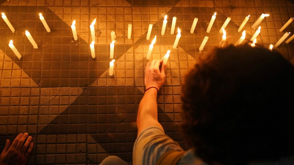 Demonstrators light candles and place them on the floor