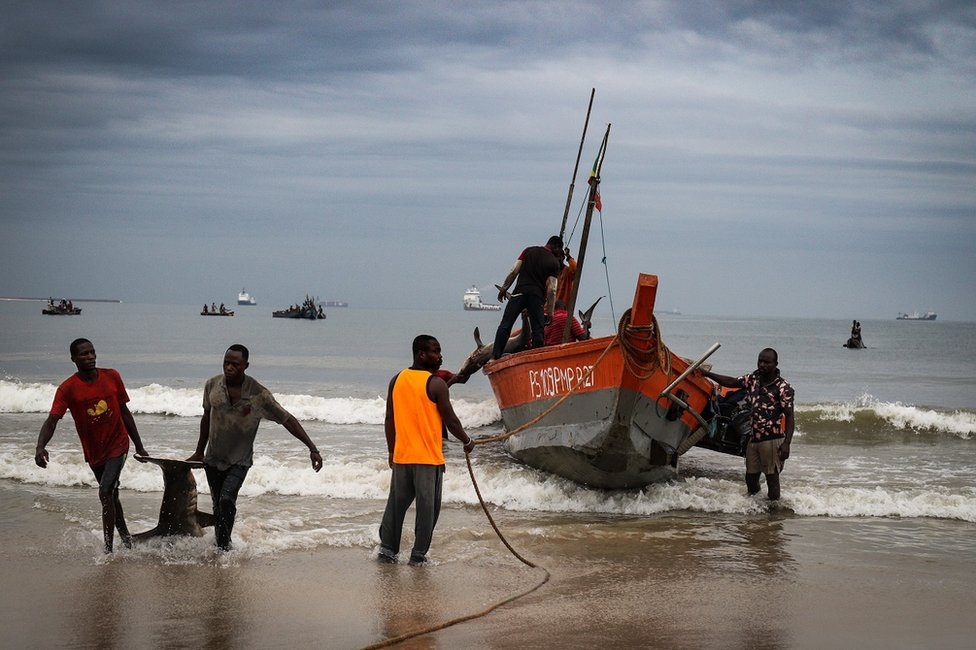 Fishermen standing by their boat