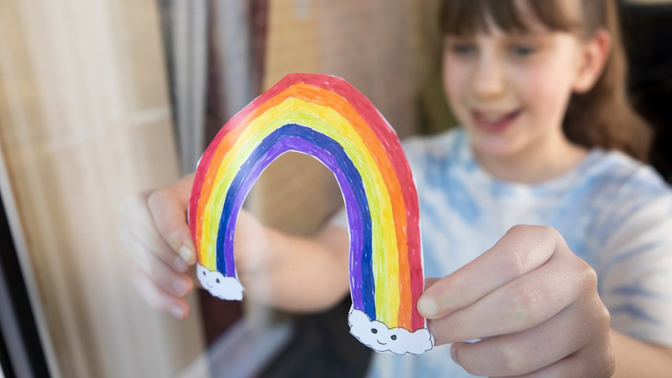 Girl holding a rainbow drawn on a piece of paper