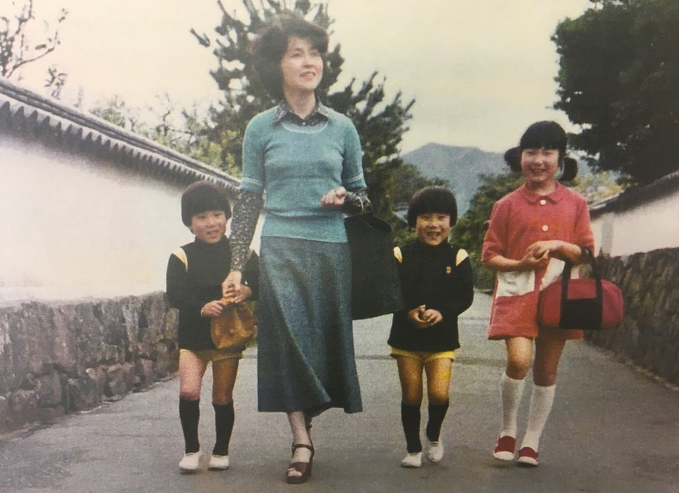A picture showing a young Sakie Yokota and her three children when they were little, smiling as they walk down a street