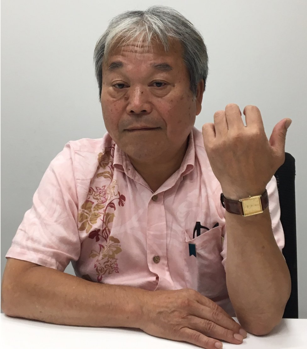 Teruaki Masumoto, in a short-sleeved shirt, holds up his wrist to show a gold watch given to him by his sister before her abduction