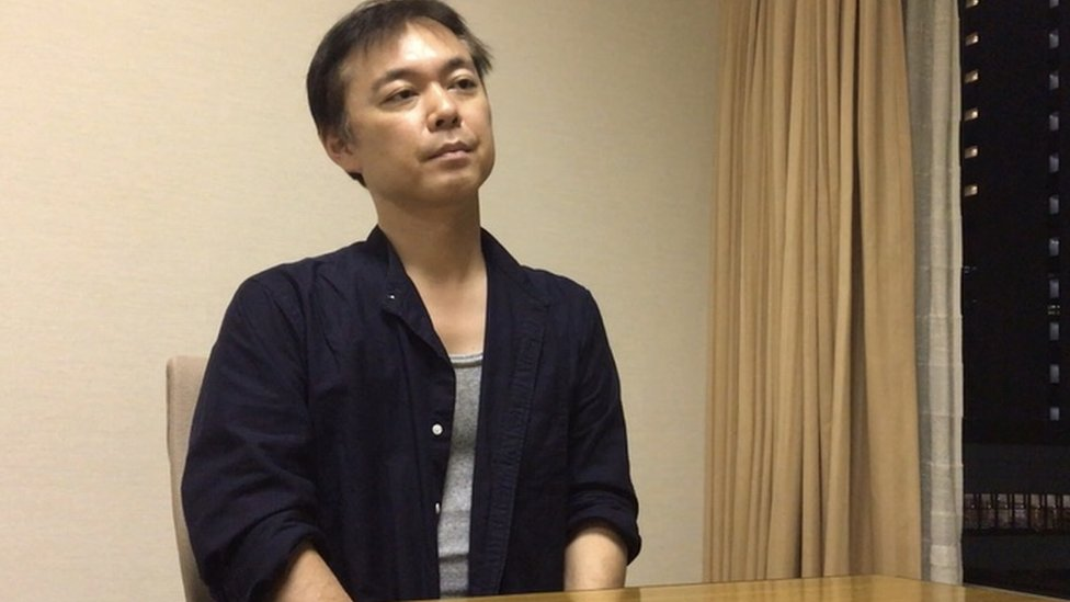 A 2020 picture of Koichiro Iizuka sitting in a conference room in Tokyo