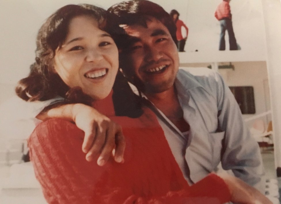A picture showing Teruaki Masumoto as a young man, with an arm round his sister. Both of them are laughing