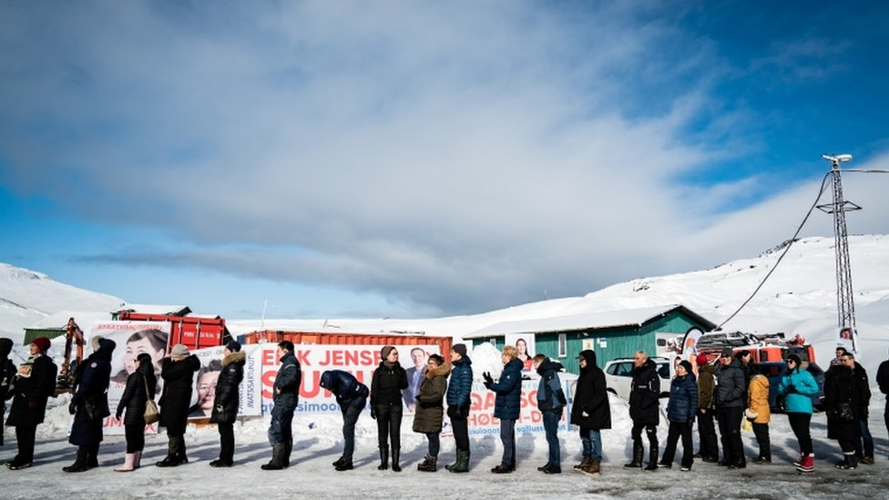 Voters stand in line waiting to cast their votes during the parliamentary election, outside the Inussivik arena, in Nuuk, Greenland