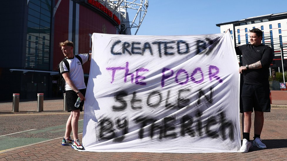"""Fans told a banner reading: """"Created by the poor, stolen by the rich"""" outside Old Trafford in Manchester"""